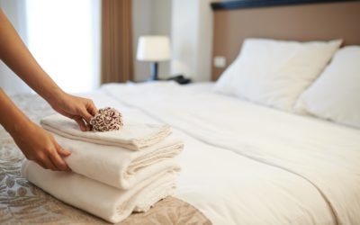 Hands of hotel maid putting flowers on the stack of towels