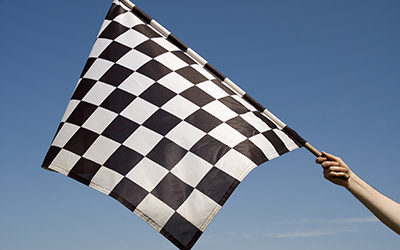 Auto racing checkered flag on a background of the  blue sky. Speedway